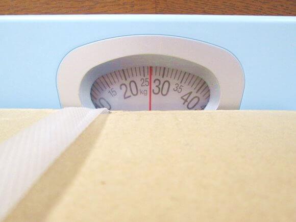 ふくれん成分無調整豆乳24本入りの重さを体重計で量っているところ